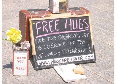 "The busker offering ""free hugs"" has a collection jar that fills up quickly"